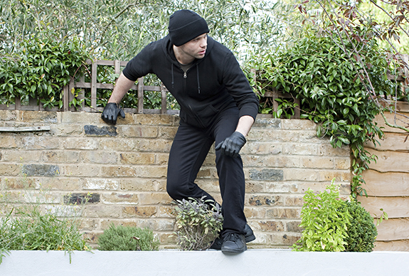 burglar-breaking-in-via-back-yard