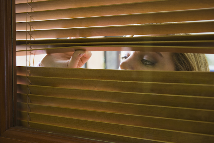 woman-peeking-through-blinds